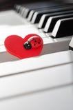 Röd hjärta med nyckelpigaprydnaden på pianotangentbordet arkivbild