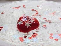 Röd hjärta med vita snöflingor Arkivbild