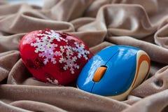 Röd hjärta- och blåttdatormus på ett beige tyg Valentin` s Arkivbilder