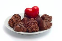 Röd hjärta och choklader på det vita tefatet Arkivfoton