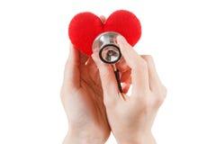 Röd hjärta och en stetoskop på vit bakgrund Arkivfoton