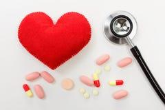 Röd hjärta och en stetoskop på vit bakgrund Fotografering för Bildbyråer