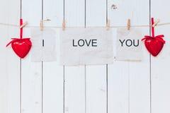 Röd hjärta och gammalt papper med text ÄLSKAR JAG DIG som hänger på clothesl Fotografering för Bildbyråer