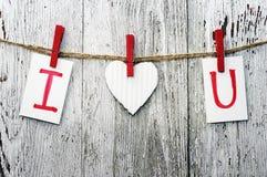 Röd hjärta- och korttext som JAG ÄLSKAR DIG, rymmer på på trätorkdukepinnor på ett rep Royaltyfri Bild