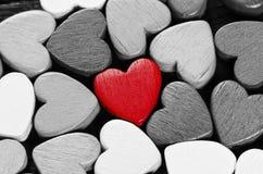 Röd hjärta och många svartvita hjärtor. Arkivbild