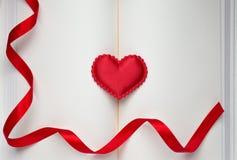 Röd hjärta och rött band på den öppna boken Royaltyfria Bilder