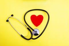 Röd hjärta och stetoskop på gul bakgrund, hjärtahälsovård och läkarundersökningteknologibegreppet, selektiv fokus, arkivbilder