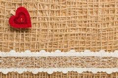 Röd hjärta på abstrakt torkdukebakgrund Arkivbilder