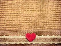 Röd hjärta på abstrakt torkdukebakgrund Arkivfoton
