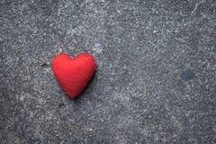 Röd hjärta på cementgolv Arkivbilder