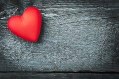 Röd hjärta på de mörka brädena Arkivbilder