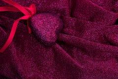Röd hjärta på den släta eleganta röda och silvriga tyglyxtorkduken Royaltyfria Foton