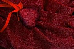 Röd hjärta på den släta eleganta röda och silvriga tyglyxtorkduken Arkivfoton