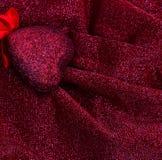Röd hjärta på den släta eleganta röda och silvriga tyglyxtorkduken Arkivbild