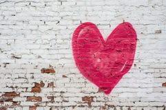 Röd hjärta på en bekymrad vit tegelstenvägg Arkivbild