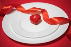 Röd hjärta på en platta valentin för dag s Royaltyfri Foto
