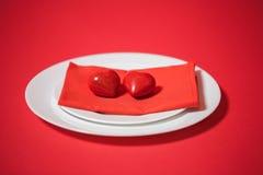 Röd hjärta på en platta valentin för dag s Royaltyfria Bilder