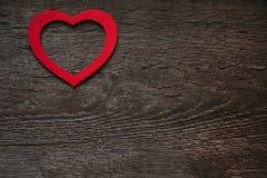 Röd hjärta på ett träbrunt valentin dagbräde arkivfoton