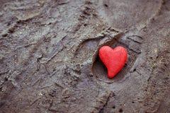 Röd hjärta på jordningen Begrepp av ensamhet, unrequited förälskelse arkivbilder