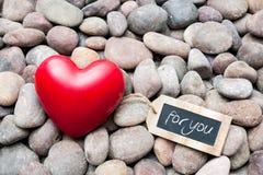 Röd hjärta på kiselstenstenar med etiketten Arkivbild