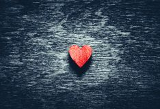 Röd hjärta på mörk träbakgrund arkivfoton