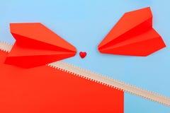 Röd hjärta på rosa färg- och blåttbakgrunden med pillinjen och pappers- flygplan royaltyfri fotografi