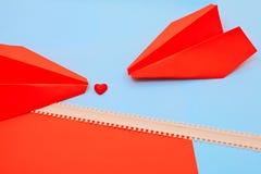 Röd hjärta på rosa färg- och blåttbakgrunden med pillinjen och pappers- flygplan arkivfoton