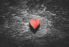 Röd hjärta på svart träbakgrund arkivbild