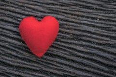 Röd hjärta på svart träbakgrund Fotografering för Bildbyråer