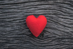 Röd hjärta på svart träbakgrund Royaltyfria Bilder