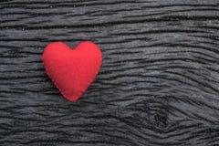 Röd hjärta på svart träbakgrund Royaltyfri Fotografi