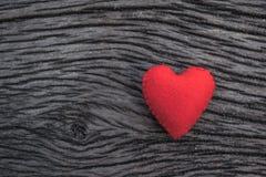 Röd hjärta på svart träbakgrund Arkivfoton