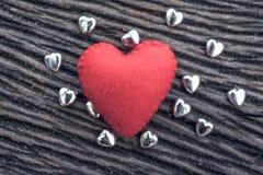 röd hjärta på svart träbakgrund med liten siverhea Royaltyfria Foton
