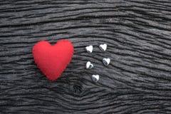 röd hjärta på svart träbakgrund med liten siverhea Fotografering för Bildbyråer