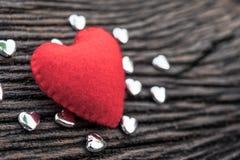 röd hjärta på svart träbakgrund med liten siverhea Royaltyfri Fotografi