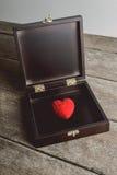 Röd hjärta på tappningsmyckenasken, som står på brädena, Royaltyfri Foto