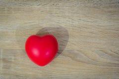Röd hjärta på trätabellen Arkivfoton