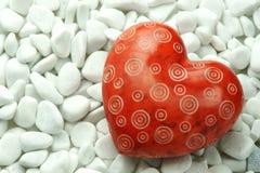 Röd hjärta på vita stenar Arkivbilder