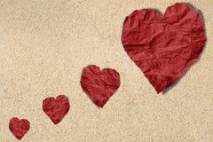 Röd hjärta skrynkligt papper på sandtextur, bakgrund för strandväntextur arkivfoton