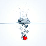 Röd hjärta som faller in i vatten Arkivfoton