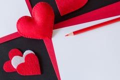 Röd hjärta som göras av filt, rött papper Arkivfoton