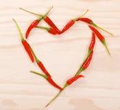 Röd hjärta som göras av glödheta chilipeppar Royaltyfri Foto
