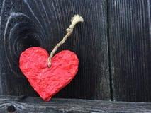Röd hjärta som göras av mer papier - mache på en gammal grå träbakgrund Royaltyfri Foto