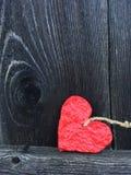Röd hjärta som göras av mer papier - mache på en gammal grå träbakgrund Royaltyfri Bild