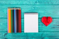 Röd hjärta som göras av papper, kulöra blyertspennor och notepaden Brevpappertillförsel origami Arkivbild