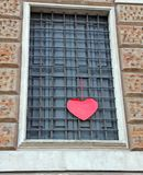 Röd hjärta som hänger på byggnaden Royaltyfria Bilder