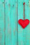 Röd hjärta som hänger vid bandet på träbakgrund för antika krickablått Arkivfoto