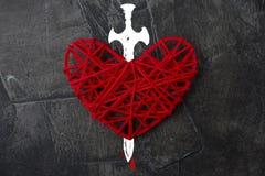 Röd hjärta som trängas igenom med ett svärd Arkivfoton