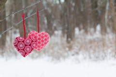 Röd hjärta som två hänger på bakgrunden för trädbänksnö Arkivbild