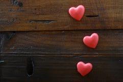 Röd hjärta tre på träbakgrund Royaltyfri Foto